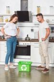 Fotografia Coppie adulte con le mani sui mucchi in piedi in cucina e guardando il verde ricicla casella