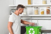 Photo handsome man putting empty plastic bottle in green recycle box