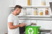Fotografia uomo adulto mettere la bottiglia di plastica vuota nella casella verde ricicla