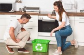 Photo adult couple standing at kitchen with green recycle box on floor