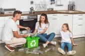 Fotografia famiglia che si siede sul pavimento in cucina e mettendo bottiglie di plastica vuote in riciclo scatola