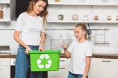 Fotografie mother and daughter putting empty plastic bottles at green recycle box together
