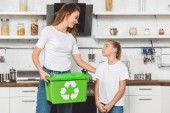 Fotografie mother holding green recycle box and looking at daughter