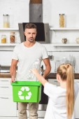 Fotografie father holding green recycle box while daughter holding empty plastic bottles