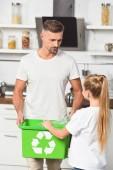 Fotografia padre e figlia mettendo bottiglie di plastica vuote a casella verde ricicla in cucina
