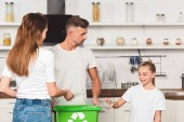 family standing at kitchen and putting empty plastic bottles in green recycle box