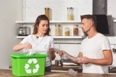Photo husband and wife standing at kitchen and putting empty plastic bottles in recycle box