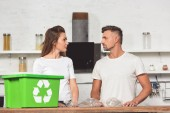 Photo adult couple looking at each other with green recycle box and empty plastic bottles at kitchen table