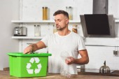 Photo handsome man putting plastic bottles in green recycle box