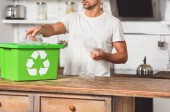 Photo cropped vie of man putting plastic bottles in green recycle box