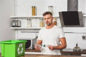 Photo handsome man holding plastic bottles with green recycle box at wooden table