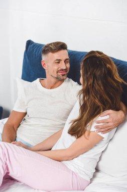 Man looking at woman and smiling in pyjamas