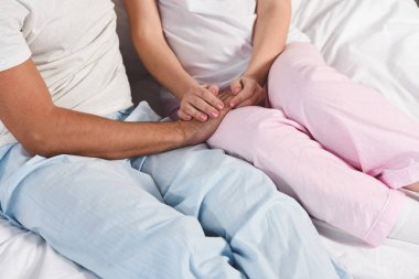 Cropped view of couple holding hands in pyjamas
