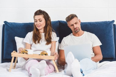 Husband using laptop and wife having breakfast in bed