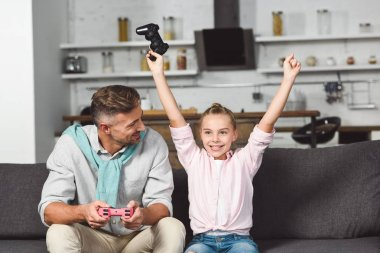happy daughter rejoicing victory while playing video game with father