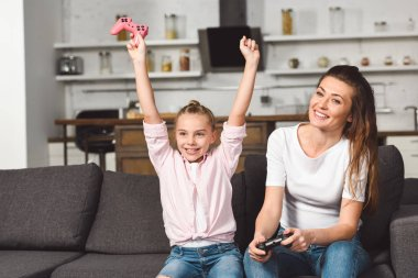 Happy daughter rejoicing victory while playing video game with mother stock vector