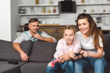 Attractive mother and daughter playing video game while father hiding behind sofa stock vector