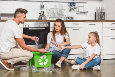 Family sitting on floor at kitchen and putting empty plastic bottles in box with recycle sign stock vector