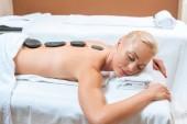 Fotografia Donna sdraiata sul lettino da massaggio con pietre calde sulla schiena