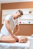Fotografie Handsome masseur doing massage to blonde woman in spa salon