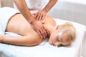 Muž masér dělá masáž na blond žena