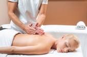 männlicher Masseur macht Rückenmassage für Frau im Schönheitssalon