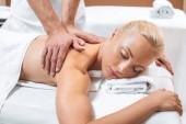 Fotografia uomo che fa i massaggi ad una donna bionda con gli occhi chiusi