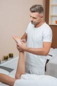 Fotografia bello massaggiatore che massaggiano piede della donna in stazione termale