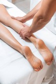 Photo cropped view of man massaging woman legs on white massage table