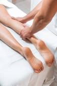 oříznutý pohled člověka masíruje žena nohy na bílý masážní stůl