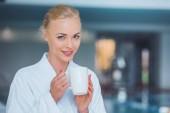 usmívající se atraktivní blondýna žena držící bílý pohár v lázních