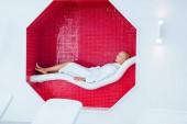 Fotografie blond žena ležící na bílé lehátko mozaika osmiúhelník