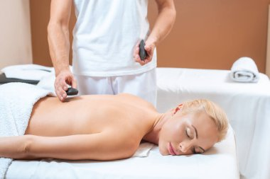 Male masseur putting hot stones on back of blonde woman