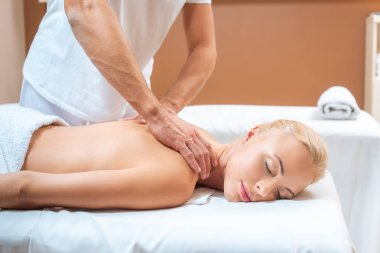Blonde woman enjoying massage of male therapist in spa