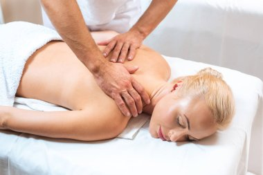 Male masseur doing massage to blonde woman