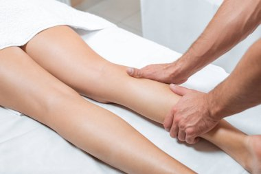 cropped view of man massaging woman legs in spa center