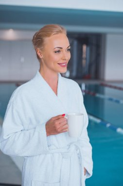 smiling attractive blonde woman holding white cup near swimming pool in spa