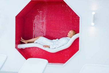 blonde woman lying on white deck chair in mosaic octagon
