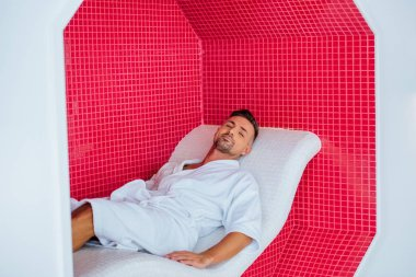 handsome man lying on deck chair near mosaic wall in spa