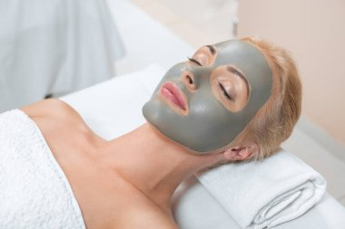 close up of blonde woman lying with facial clay mask in spa