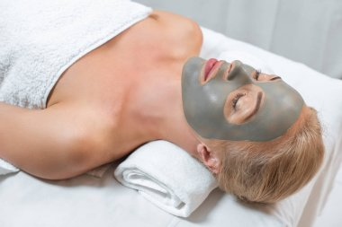 close up of woman lying with closed eyes and facial clay mask in spa