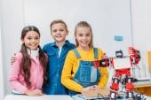 spokojený spolužáci stojící vedle robota po stonku robotiky lekce