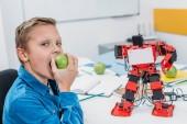 Photo cheerful boy eating apple after STEM robotics lesson