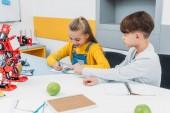 Fotografie děti psaní v poznámkové bloky na lekci o robotice kmenových