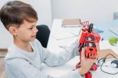 Fényképek mosolyogva iskolás gazdaság piros robot készült műanyag építőelemek szára osztályban