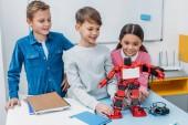 Photo happy schoolchildren touching red handmade robot at desk in stem class