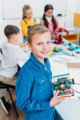 Photo smiling schoolboy holding robot and looking at camera with classmates at background in classroom