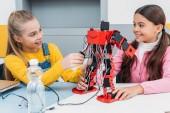 Fotografie s úsměvem školačky konstrukci červené robota ve vědě třídě