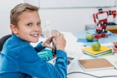 Fotografie schoolboy sitting at desk and looking at camera in stem education class