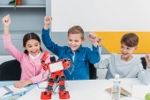 Fotografie happy schoolchildren raising hands and looking at red handmade robot at desk during STEM lesson